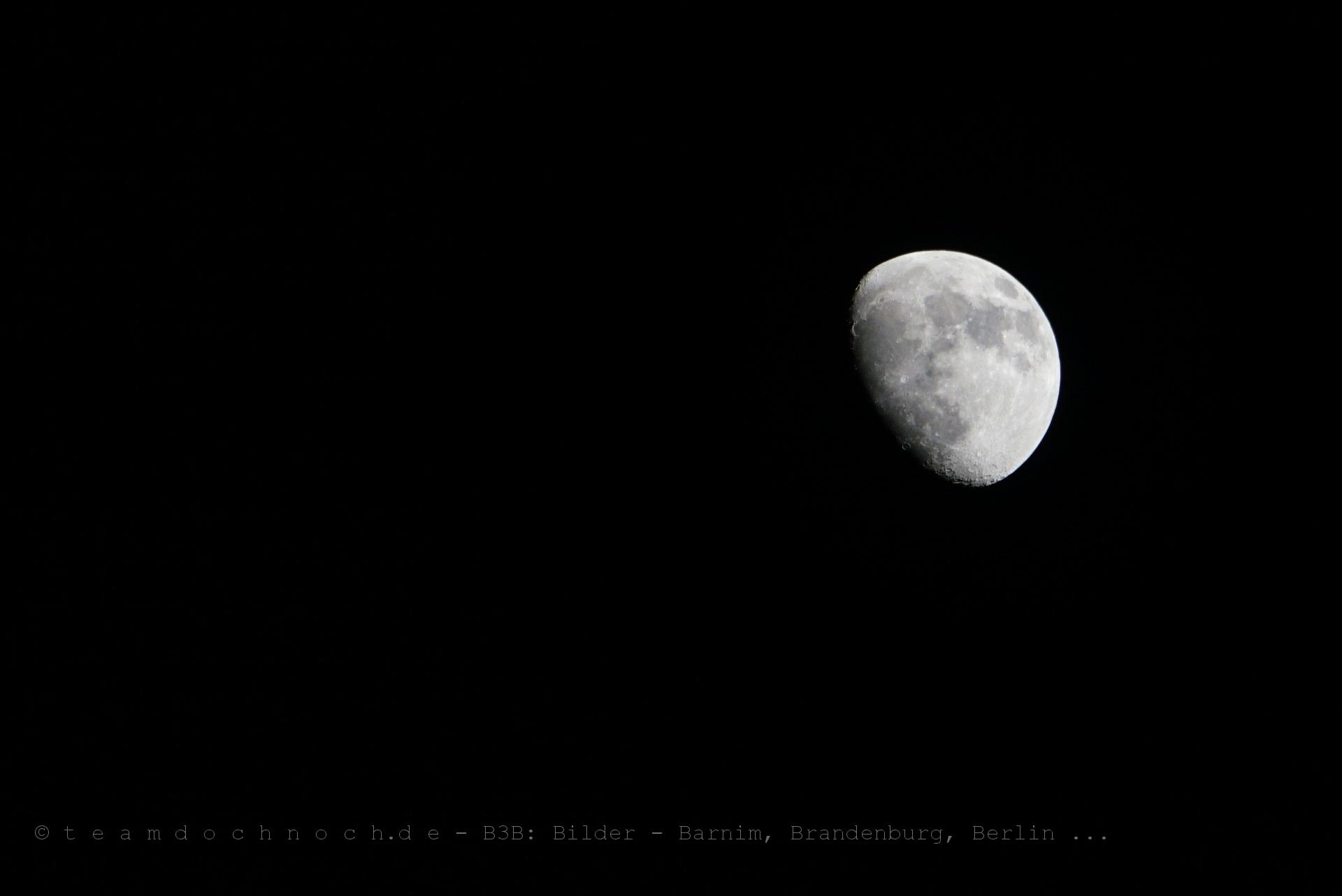 Ein zunehmender Mond über der Stadt